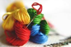 Aiguille dans la toile avec des fils de différentes couleurs pour la broderie Fin de macro de broderie  Photo stock