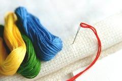 Aiguille dans la toile avec des fils de différentes couleurs pour la broderie Fin de macro de broderie  Photographie stock