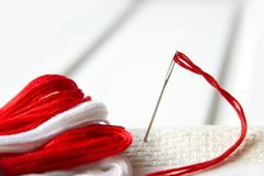 Aiguille dans la toile avec le fil rouge pour la broderie Fin de macro de broderie  Photographie stock
