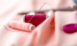 Aiguille de couture, bobines de fil et tissu Images libres de droits