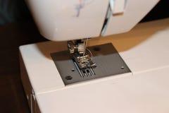 Aiguille de machine à coudre et plan rapproché blancs de titre de bas de page Image stock