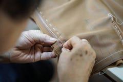 Aiguille de main de grand-maman et couture faisant le tissu Images libres de droits