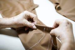 Aiguille de main de grand-maman et couture faisant le tissu Photographie stock