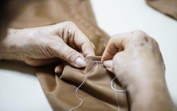 Aiguille de main de grand-maman et couture faisant le tissu Image stock