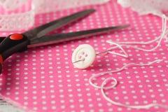Aiguille et bouton sur le tissu rose de point de polka Images stock