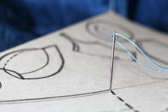 Aiguille et fil sur le modèle de couture Photographie stock