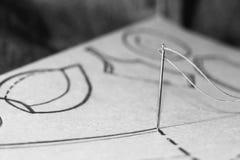 Aiguille et fil sur le modèle de couture Photo stock