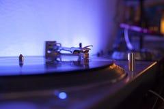 Aiguille jouant le disque de vinilo sur une lumière menée bleue Images stock