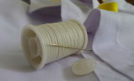Aiguille sur la bobine de fil et le bouton blanc Photographie stock