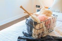 Aiguilles de fil et de crochet dans un panier en acier sur un lit Photo libre de droits