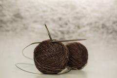 Aiguilles de tricotage et boule de laine Photo stock