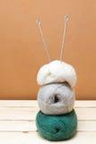 Aiguilles de tricotage et boules de laine sur une table en bois Photos stock