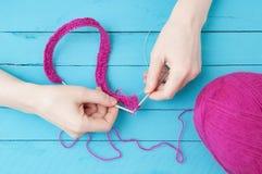 Aiguilles de tricotage pour tricoter dans les mains d'un écheveau de fil rose photo stock