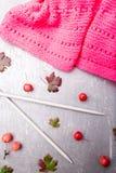 Aiguilles de tricotage proches d'écharpe rose sur le fond gris Vue supérieure Copiez l'espace Images stock
