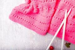 Aiguilles de tricotage proches d'écharpe rose sur le fond gris Vue supérieure Copiez l'espace Image stock