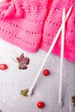 Aiguilles de tricotage proches d'écharpe rose sur le fond gris Vue supérieure Copiez l'espace Configuration plate Image libre de droits