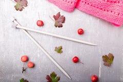 Aiguilles de tricotage proches d'écharpe rose sur le fond gris Vue supérieure Copiez l'espace Configuration plate Photo stock