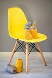 Aiguilles et fil de crochet dans le panier tricoté sur la chaise jaune Image stock