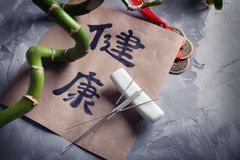 Aiguilles et papier d'acuponcture avec des hiéroglyphes photographie stock