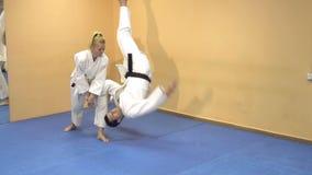 Aikido för kampsportförlageövning med en kvinna arkivfilmer