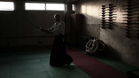 Aikido fighter with sword at sports hall stock footage