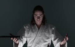 Aikido man looking at katana(sword) Royalty Free Stock Photos