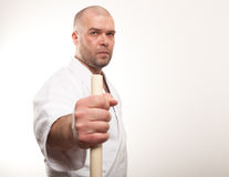 Aikido man with a stick. Man with a stick on light background royalty free stock photo