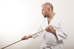 Aikido man with a stick. Man with a stick on a light background royalty free stock photography