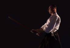Aikido practicer Aikidoka mit einer hölzernen Klinge des Trainings boken dunkles Dojofoto Lizenzfreie Stockbilder