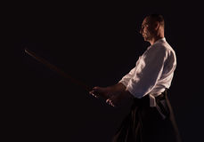 Aikido practicer Aikidoka with a training wooden sword boken dark dojo photo Royalty Free Stock Images