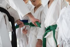 Aikido trainer tying belt for his pupil before competition royalty free stock photography