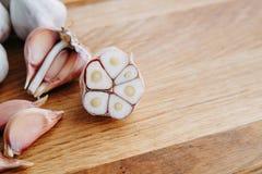Ail, clous de girofle d'ail et ampoules coupés en tranches d'ail sur le backgrou en bois Photographie stock