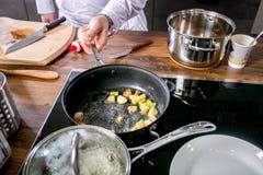 Ail de friture de chef dans une casserole Classe principale dans la cuisine Le processus de la cuisson Point par point d'instruct photo stock