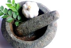 Ail et feuilles fraîches de cari dans le mortier et le pilon en pierre Photos libres de droits