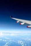 Aile d'avion au-dessus des nuages Image stock
