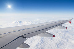 Aile d'avion au-dessus des nuages et du soleil Photographie stock