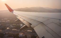 Aile d'avion avec la montagne et ville de vue aérienne Images stock