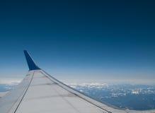 Aile d'avion de ligne à réaction commercial au-dessus des nuages et de la montagne Photos stock