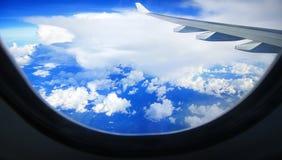 Aile d'avion en ciel bleu avec nuageux ci-dessous Image stock