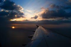 Aile d'avion en vol de fenêtre, ciel de coucher du soleil Photos libres de droits