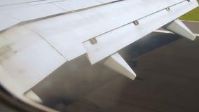 Aile d'avion pendant l'atterrissage avec des ailerons vers le bas sur le ciel au-dessus de la terre banque de vidéos
