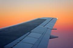 Aile d'avion sur le coucher du soleil photos libres de droits