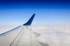 Aile d'avions au-dessus des nuages Images stock