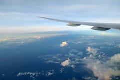 Aile d'avions au-dessus des nuages dans la lumière de coucher du soleil Photographie stock libre de droits