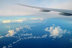 Aile d'avions au-dessus des nuages dans la lumière de coucher du soleil Photo libre de droits