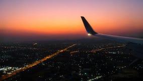 Aile d'avions dans le ciel avec le ciel de coucher du soleil et le backgrou léger de ville photos stock