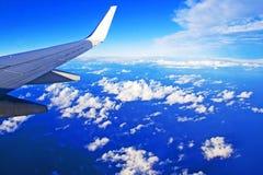 Aile d'un avion sur un ciel bleu avec des cumulus d'une fenêtre d'avion photographie stock libre de droits