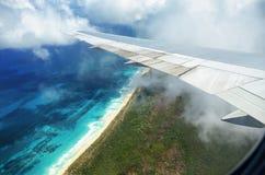 Aile d'un vol d'avion au-dessus des nuages au-dessus de l'île tropicale Image libre de droits