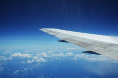 Aile d'un vol d'avion au-dessus des nuages au-dessus de l'île tropicale Photo libre de droits