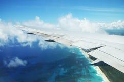 Aile d'un vol d'avion au-dessus des nuages au-dessus de l'île tropicale Images stock
